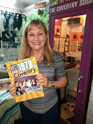 Smiling woman holding a book called The Dirty Stop Puts Guide to 1970s Coventry