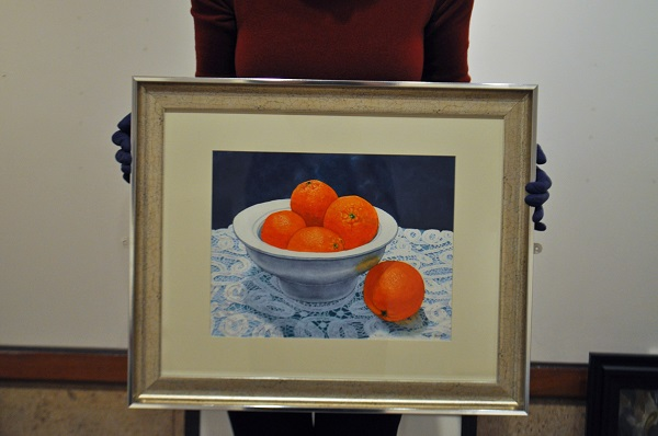a painting of oranges on white lace against a blue background