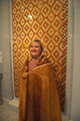 a smiling woman tries on a decorative wrap