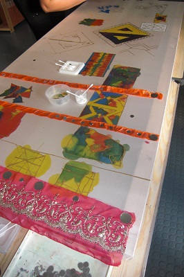 textiles are glued on to a large piece of paper