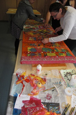 Families adding textiles and sequins to the artwork