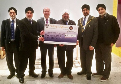 A group of men hold a giant cheque for £501