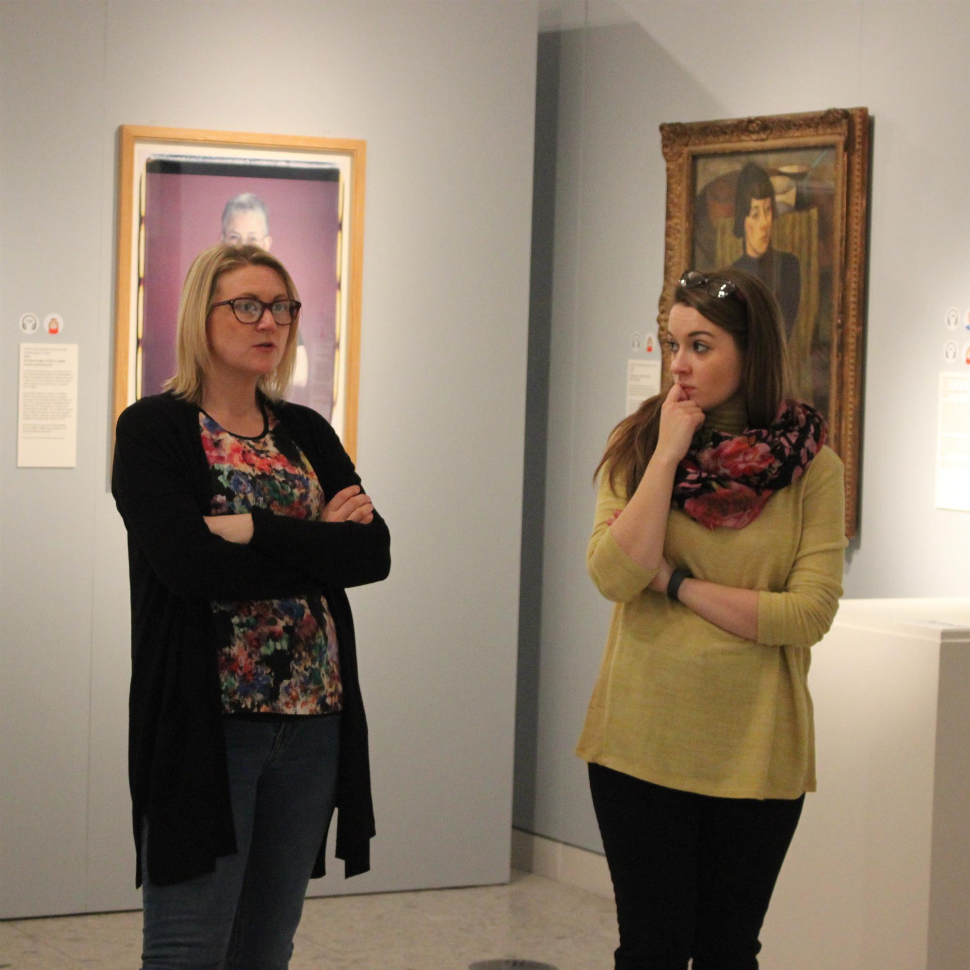 Two thoughtful women stand in front of portraits