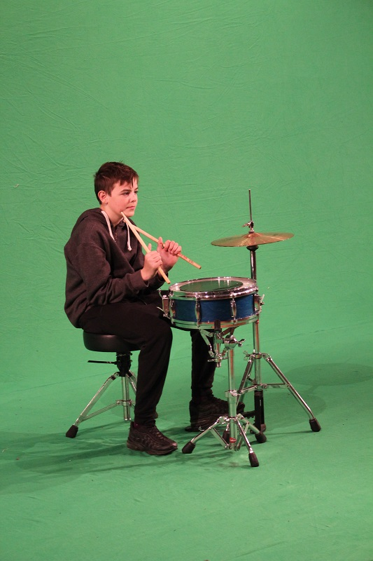 boy with drum kit against green screen