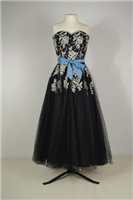 1953 evening dress. This is an evening dress bought by the donor in 1953 and it has a matching net jacket or bolero. Strapless dresses were very fashionable in the 1950s. Full skirts like the one on this dress were held out with layers of stiff petticoats