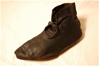 A rare complete leather medieval shoe, worn by a woman.