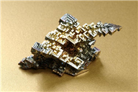 Bismuth. This particular crystal was artificially created in a laboratory. Its distinctive colouring make it a popular and attractive crystal. In its natural form bismuth is a silvery-white metallic element.