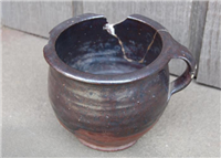 This is a Tudor chamber pot made of blackware.